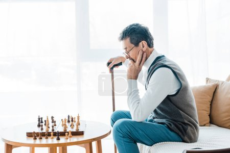 Photo for Thoughtful pensioner in glasses looking at chess board and holding walking stick - Royalty Free Image