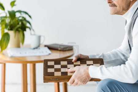 Photo for Cropped view of senior man sitting and holding chess board at home - Royalty Free Image