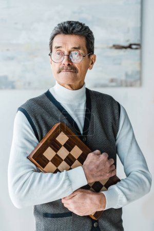 Photo for Pensive senior man holding chess board at home - Royalty Free Image
