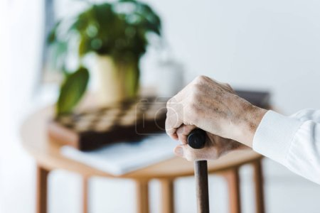 Photo for Cropped view of pensioner holding walking cane at home - Royalty Free Image