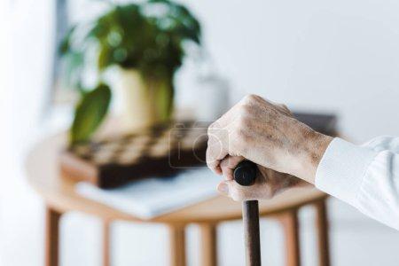 Photo pour Recadrée vue du pensionné tenant la canne à la maison - image libre de droit
