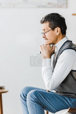 Photo for Sad pensioner sitting on sofa at home - Royalty Free Image