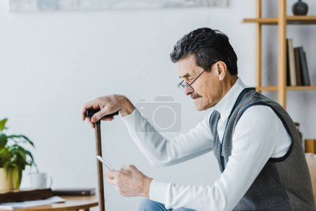 Photo for Upset senior man with mustache sitting on sofa and using smartphone at home - Royalty Free Image