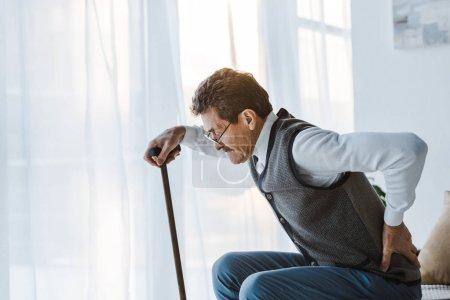Photo pour Homme âgé avec canne à pied tenant en arrière tout en se tenant debout du canapé - image libre de droit