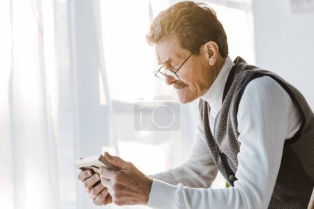 Photo pour Pensionné triste avec moustache en regardant la photo en cadre photo tout en étant assis à la maison - image libre de droit