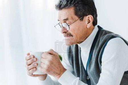 Photo pour Senior homme dans des lunettes tenant tasse avec boisson dans les mains - image libre de droit
