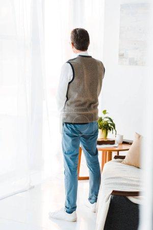 Foto de Vista posterior de senior hombre de pie en la sala de estar - Imagen libre de derechos