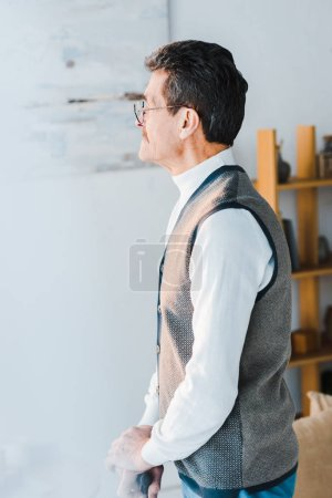 Photo for Senior man with grey hair standing in living room - Royalty Free Image