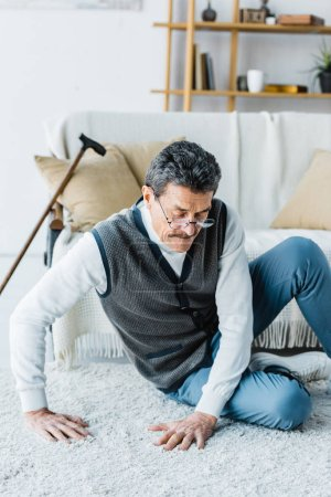 Foto de Hombre jubilado sentado cerca de bastón en alfombras en casa - Imagen libre de derechos