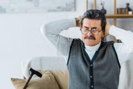 Photo pour Homme senior dans des verres assis avec les yeux fermés tout en ayant des maux de tête - image libre de droit