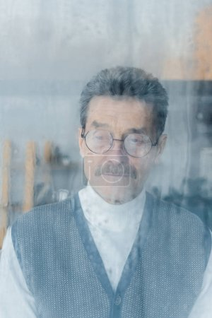 Photo for Sad senior man in glasses standing at home near window - Royalty Free Image