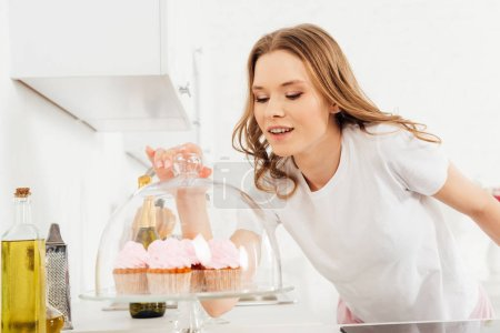 beautiful smiling girl in pajamas holding dome from glass stand with pink cupcakes in kitchen