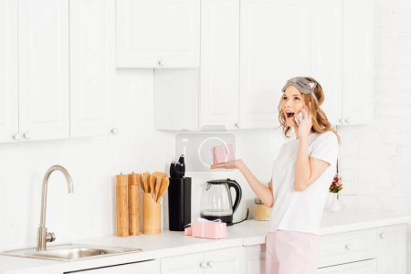 Photo pour Beautiful excited girl in pajamas and sleeping mask holding gift box and talking on smartphone in kitchen - image libre de droit