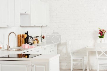 Photo for Moden interior design of kitchen with white furniture and induction cooker - Royalty Free Image