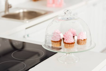 Photo for Selective focus of glass stand with pink cupcakes and dome near induction cooker in kitchen - Royalty Free Image