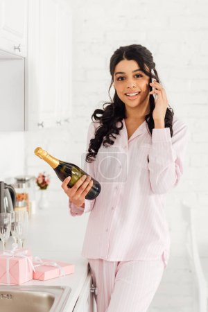 Photo for Beautiful smiling african american girl holding bottle of champagne while talking on smartphone - Royalty Free Image