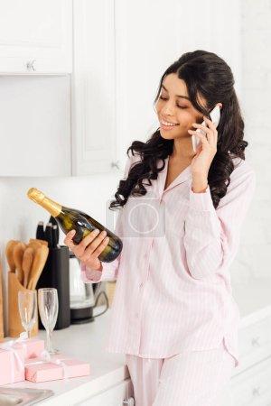 Photo pour Belle fille afro-américaine souriante tenant la bouteille de champagne tout en parlant sur smartphone - image libre de droit