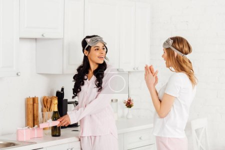 Photo for Girl clapping and congratulating smiling african american female friend with international womens day during pajama party - Royalty Free Image