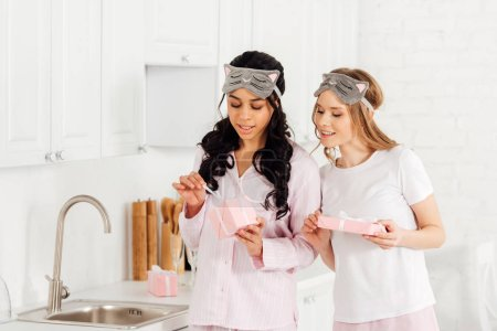 Photo for Beautiful multicultural girls in sleeping masks and pajamas opening gift boxes in kitchen - Royalty Free Image