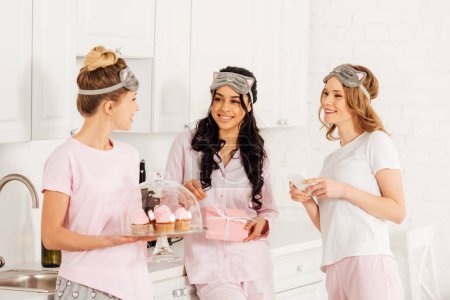 Photo for Beautiful multicultural girls using smartphone, holding cupcakes and gift box during pajama party in kitchen - Royalty Free Image