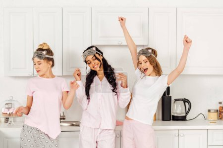 Photo for Beautiful multicultural girls in sleeping masks dancing and having fun in kitchen during pajama party - Royalty Free Image