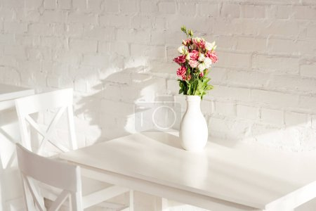 Photo for Flower bouquet in vase on white table with chairs and brick wall in kitchen - Royalty Free Image