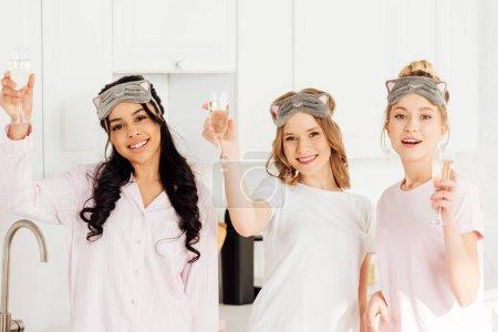 Foto de Hermosas chicas multiculturales en durmiendo mascarillas celebrando con champán y mirando a cámara durante la fiesta de pijamas - Imagen libre de derechos