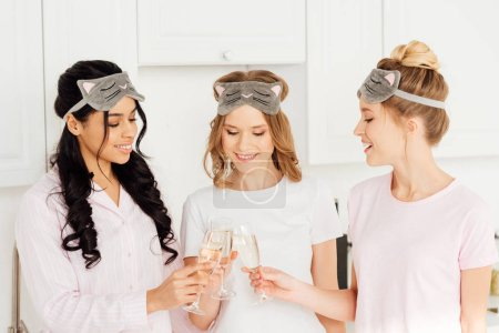 Photo for Beautiful multicultural girls in sleeping masks celebrating and clinking champagne glasses during pajama party - Royalty Free Image
