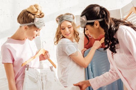 Photo for Selective focus of beautiful smiling multicultural girls choosing clothes in wardrobe during pajama party in morning - Royalty Free Image