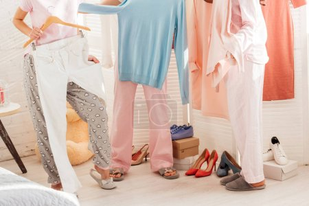 Photo for Cropped view of girls choosing clothes in wardrobe - Royalty Free Image