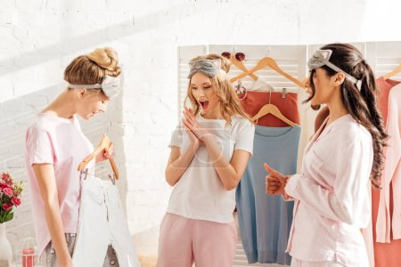 Photo for Beautiful multicultural girls choosing clothes in wardrobe during pajama party in morning - Royalty Free Image