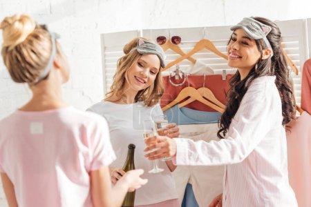 Foto de Enfoque selectivo de bellas mujeres multiculturales dormir máscaras celebrando con champán en su casa durante la fiesta de pijamas - Imagen libre de derechos