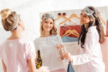 Foto de Hermosas chicas sonrientes multiculturales dormir máscaras celebrando con champán en su casa durante la fiesta de pijamas - Imagen libre de derechos