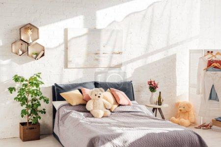 Modernes Interieur des Schlafzimmers mit Teddybär-Spielzeug, Kissen, Pflanzen und Bett