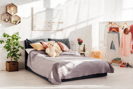 modern interior design of bedroom with teddy bear toys, pillows, clothes on racks and bed