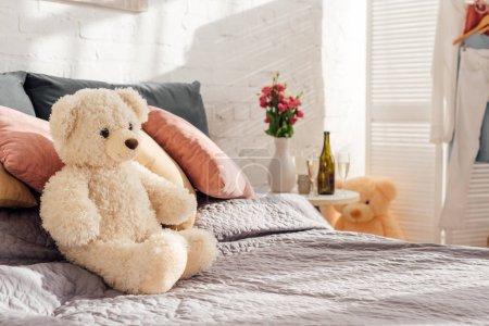 Foto de Enfoque selectivo del juguete del oso de peluche en la cama en un dormitorio moderno con espacio de copia - Imagen libre de derechos