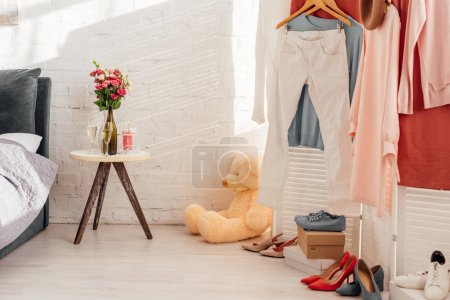 Photo for Interior desgn of bedroom with table, flowers, teddy bear toy, clothes and footwear - Royalty Free Image