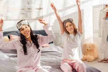 Photo for Beautiful smiling multicultural girls looking at camera and stretching in morning during pajama party - Royalty Free Image