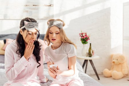 Photo for Beautiful multicultural girls in sleeping masks sitting on bed and using smartphone during pajama party - Royalty Free Image