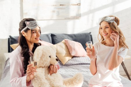 Photo for Beautiful girl in sleeping mask talking on smartphone while african american girl holding champagne glass during pajama party - Royalty Free Image