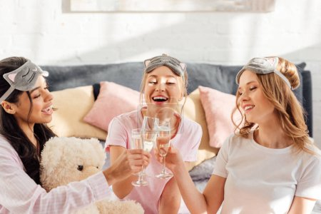 Photo for Beautiful happy multicultural girls in sleeping masks clinking champagne glasses during pajama party - Royalty Free Image