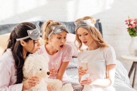 Foto de Hermosa sorpresa multiculturales chicas dormir máscaras con copas de champagne con smartphone durante la fiesta de pijamas - Imagen libre de derechos