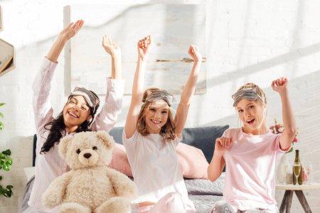 Foto de Bella sonriente a multiculturales Chicas mirando a cámara y que se extiende por la mañana en pijama party - Imagen libre de derechos