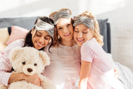 Photo for Beautiful happy multicultural girls in sleeping masks hugging in morning during pajama party - Royalty Free Image