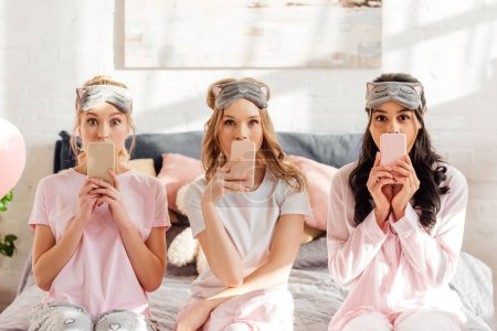 Photo for Beautiful multicultural girls in sleeping masks sitting on bed and covering mouths with smartphones during pajama party - Royalty Free Image