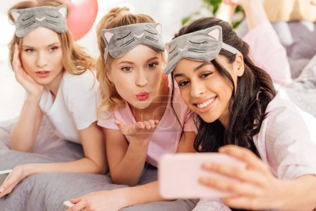 Photo for Beautiful smiling multicultural girls in sleeping masks lying in bed and taking selfie on smartphone during pajama party - Royalty Free Image