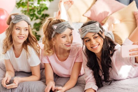 Foto de Hermosas chicas sonrientes multiculturales dormir acostado en la cama y tomar selfie en smartphone durante la fiesta de pijamas de máscaras - Imagen libre de derechos