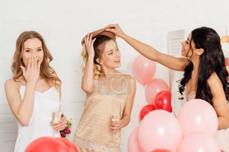 Photo for Beautiful smiling multiethnic girls in nightwear celebrating with glasses of champagne and balloons during pajama party - Royalty Free Image