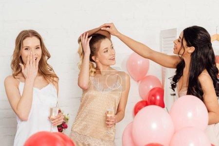 Foto de Bella sonriente a multiétnicas chicas en ropa de dormir celebrando con copas de champagne y globos durante la fiesta de pijamas - Imagen libre de derechos