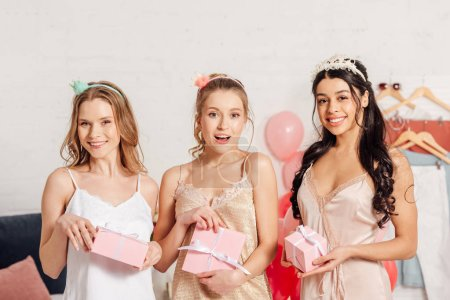 Photo for Beautiful smiling multicultural girls in nightwear holding pink gift boxes and looking at camera during pajama party - Royalty Free Image